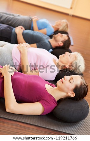 Mixed group in yoga class relaxing in a fitness center - stock photo