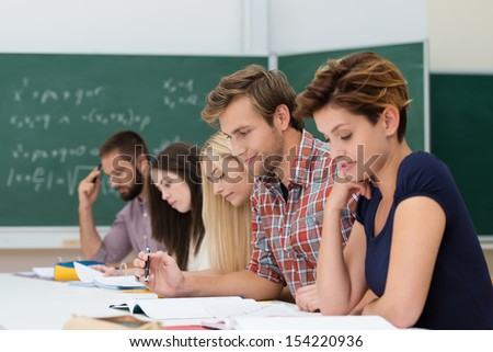 Mixed group of Caucasian determinated students studyng, looking at their notes at their desks in the class, with a chalkboard in the background - stock photo