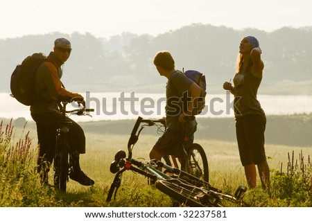 Mixed group of cyclists at sunset - stock photo
