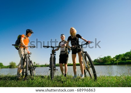 mixed group of cyclists beside river - stock photo