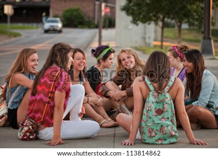 Mixed group of 8 female students sitting on the ground - stock photo
