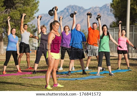 Mixed group of men and women lifting weights outdoors - stock photo
