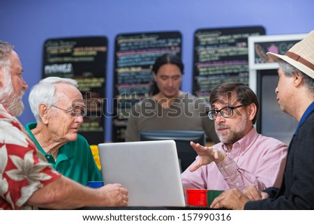 Mixed group of men in cafe having a conversation - stock photo