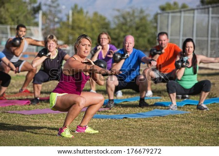 Mixed group of people doing a boot camp exercise class - stock photo