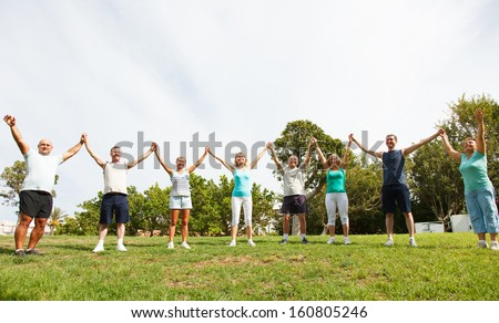 Mixed group of people joined with hands lifted high - stock photo