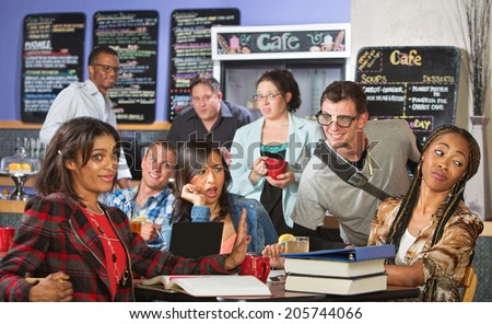 Mixed group of students annoyed with nerd in cafe - stock photo
