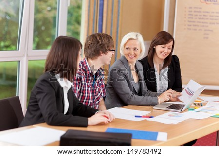 mixed group working on table in a meeting - stock photo