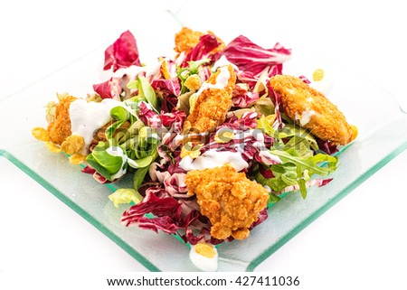 mixed lettuce salad with fried chicken in corn flakes on glass plate isolated on white background, product photography for restaurant or healthy lifestyle