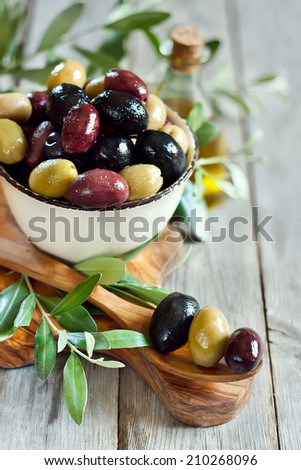 Mixed marinated olives (green, black and purple) in ceramic bowl and ...