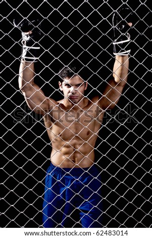 Mixed martial artist posed behind chain link - stock photo