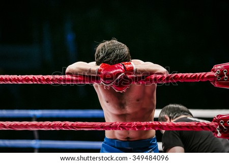 mixed martial arts fighter (MMA) stands in corner ring. lost fight. defeat of an opponent - stock photo