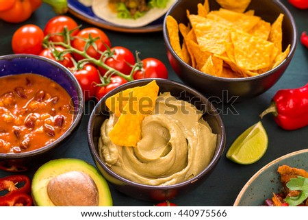Mixed mexican food. Party food. Guacamole, nachos, fajita, meat tacos, salsa, peppers, tomatoes on a wooden table. From above. Tex-mex cuisine. Assorted appetizers. Cuisine of Mexico. Selective focus - stock photo