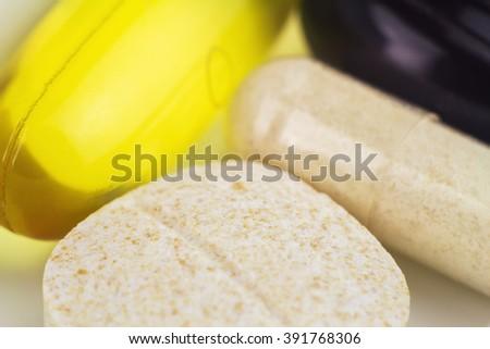 Mixed natural food supplement pills, omega 3, vitamin c, carotene, glucosamine capsules, macro image, selective focus - stock photo