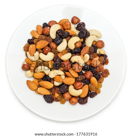 Mixed nuts and dry fruits in plate isolated on white background - stock photo