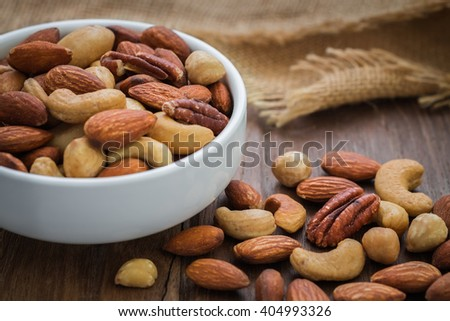 Mixed nuts on wooden table and bowl  - stock photo