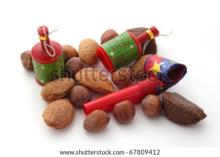 Mixed nuts with party blowers and poppers on a plain white background. - stock photo