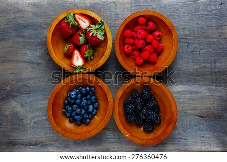 Mixed of berries (strawberries, raspberries, blueberries and blackberries) in wooden bowls on dark background. Agriculture, Gardening, Harvest Concept. Top view. - stock photo
