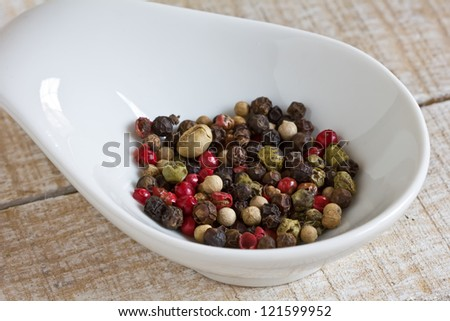 Mixed pepper in bowl on wooden background. Selective focus.