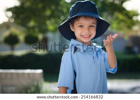 Mixed race Asian Caucasian boy confidently leaves home on his first day of school. Wearing uniform and sun hat. Turning to blow a kiss to his mom as he leaves his house. - stock photo