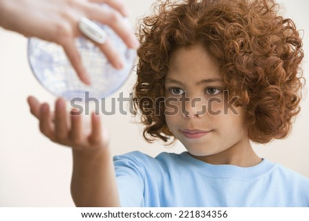Mixed Race boy reaching for globe - stock photo