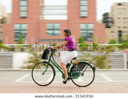 mixed-race businesswoman going to work by bike. - stock photo