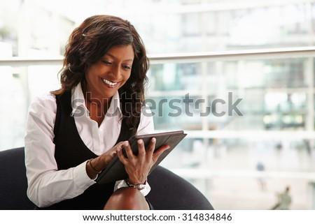 Mixed race businesswoman using digital tablet, waist up - stock photo