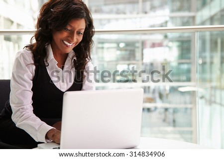 Mixed race businesswoman using laptop computer - stock photo
