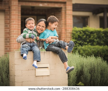 Mixed race children with their Asian mother play in front of their family home. Image captures family love, confidence, cheerfulness, and togetherness at home. - stock photo