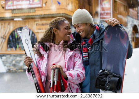 Mixed race couple with snow skis - stock photo