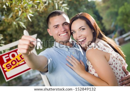 Mixed Race Excited Military Couple with New House Keys and Sold Real Estate Sign Outside. - stock photo
