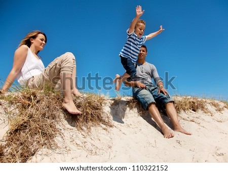 Mixed race family enjoying their summer vacation outdoors - stock photo