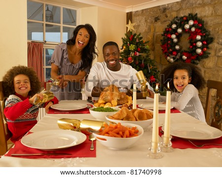 Mixed race family having Christmas dinner
