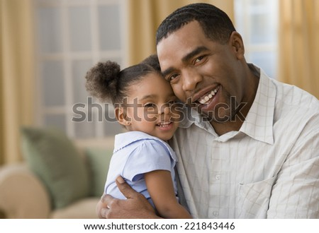 Mixed Race father and daughter hugging - stock photo