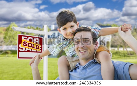 Mixed Race Father and Son Celebrating with a Piggyback in Front Their House and Sold Real Estate Sign. - stock photo