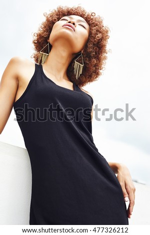 Mixed race female model with curly hair and wearing black dress at tthe outdoor