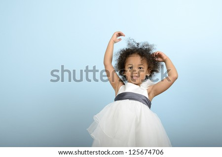 Mixed race girl holding up her arms - stock photo
