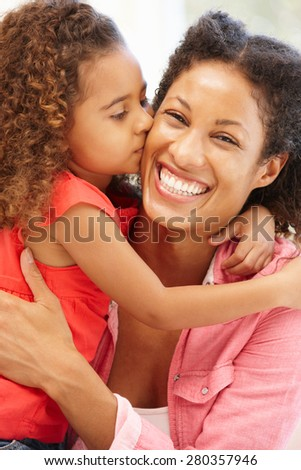 Mixed race girl kissing mother - stock photo