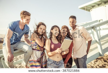 Mixed race group of friends enjoying time together on the beach watching funny videos on the social networks - stock photo