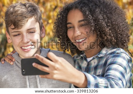 Mixed race group of two happy children teenagers, African American girl caucasian boy laughing together and taking selfie photograph on cell phone smartphone - stock photo