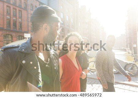 Mixed race group walking in Hamburg, Germany. Four persons, with different ethnicities and wearing urban style clothes, looking each other and smiling. Lifestyle and friendship concepts.