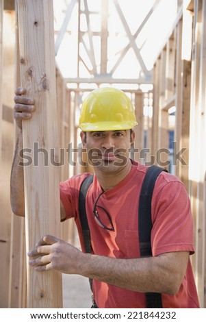 Mixed Race male construction worker holding lumber