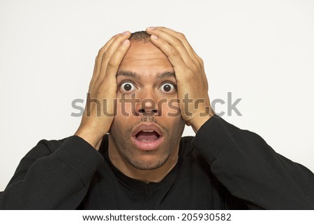 Mixed race male with his hands on his head looking in absolute shock, awe and disbelief - stock photo