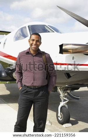 Mixed Race man in front of airplane