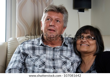 Mixed race mature couple sitting close together - stock photo
