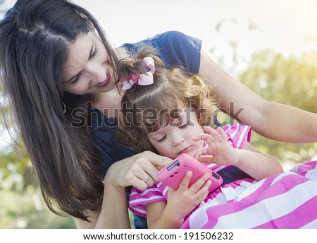 Mixed Race Mother and Cute Baby Daughter Playing with Cell Phone in Park. - stock photo