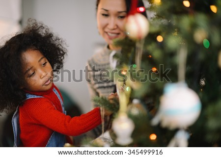 Mixed race mother and daughter decorating Christmas tree - stock photo