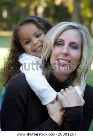 Mixed race mother and daughter enjoying the park - stock photo