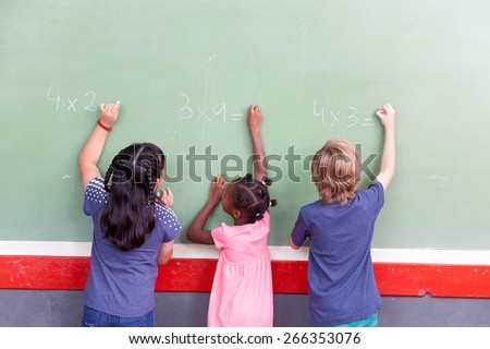 Mixed race school children writing on chalkboard. - stock photo