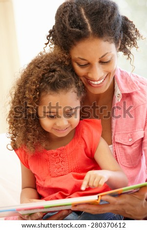 Mixed race woman and daughter reading - stock photo