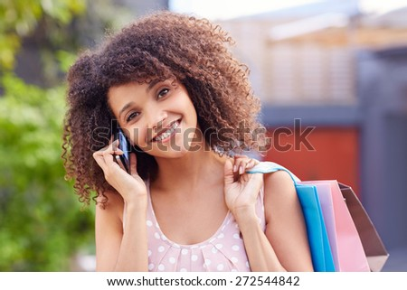 Mixed race woman listening to her mobile phonw while holding bags of shopping over her shoulder - stock photo
